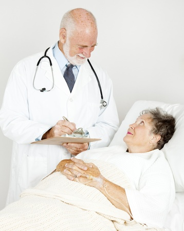 Doctor on his rounds, talking to a patient in the hospital.   photo