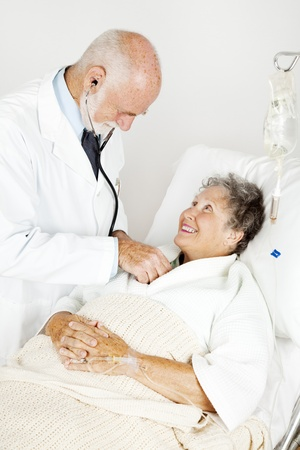Doctor using his stethoscope to listen to an elderly hospital patient's heart.