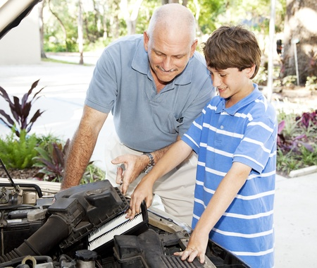 Father shows his son how to put a clean air filter in the car engine.