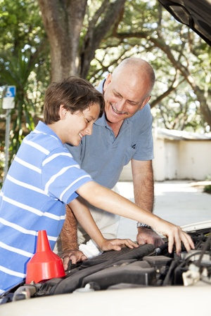 Father and son having fun together repairing the family car.   photo