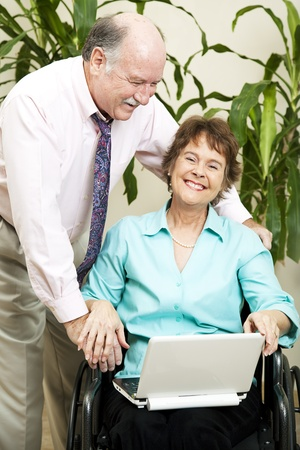 Disabled businesswoman and her boss laughing together as they surf the internet.   photo