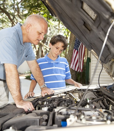 Little boy watching his father repair the family car.   photo