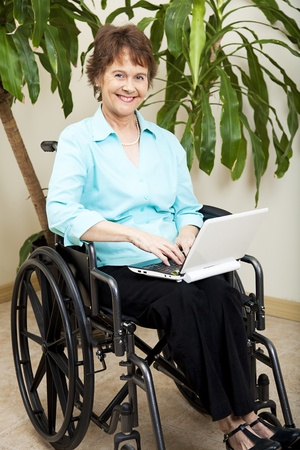 Pretty businesswoman in a wheelchair, using a netbook to wirelessly surf the internet.   photo