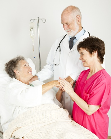 hospice: Attentive doctor and nurse caring for an elderly hospital patient.