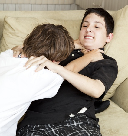 Two brothers playfully fighting on the couch.