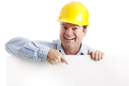 işçi: Construction worker leaning over and pointing to blank white space.  Isolated.