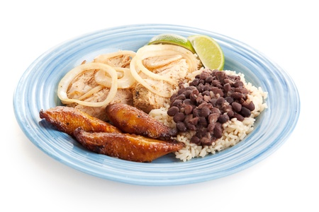 Delicious Cuban dinner with roast pork, black beans and rice, and fried plantains.  Isolated on white background Banco de Imagens