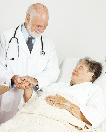 Friendly doctor comforting a senior hospital patient.