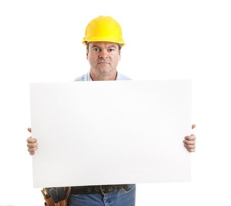 あなたのテキストの準備ができて、空白の白の兆候を運んで深刻な建設労働者。白で隔離されます。 写真素材