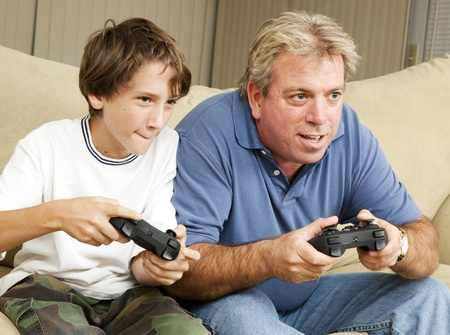 Uncle and nephew (or father and son) playing video games together.   Stock Photo - 9418925