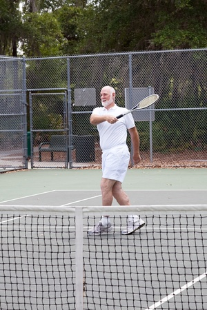 Active senior man plays tennis for exercise and fun.   photo