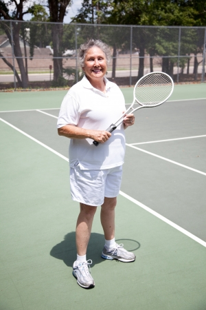 Portrait of active senior woman  on the tennis courts.   photo