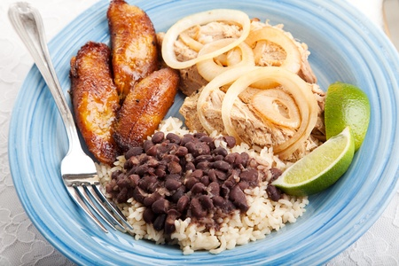 Cuban dinner, consisting of roast pork, black beans and rice, and fried sweet plantains.