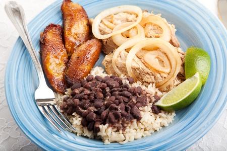 Dîner cubain, composé de rôti de porc, de haricots noirs et de riz et de plantain sweet frit.   Banque d'images