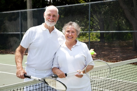 Portrait of a happy senior couple on the tennis courts.   photo