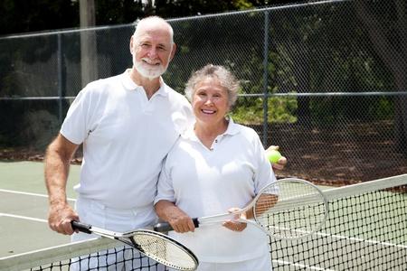 raqueta de tenis: Retrato de una feliz pareja alta en las canchas de tenis.