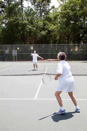 Senior man and woman playing in a tennis match.   photo