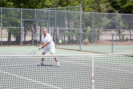 Retired senior woman plays tennis for fun and exercise. photo
