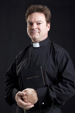 religion catolica: Retrato de sacerdote sosteniendo una Biblia.  Fondo negro.