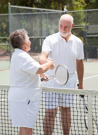 Senior couple shakes hands over the net on the tennis court. Stock Photo - 9420934