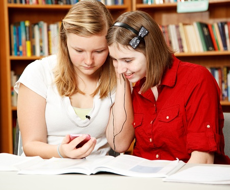 Two pretty teen girls in the school library, listening to an mp3 player. Stock Photo - 9527866