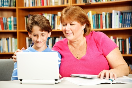 Mother (or teacher) helps her young son study on a computer in the library.   Stock Photo - 9537263
