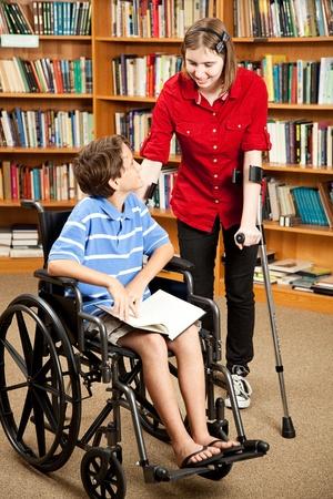 前腕松葉杖、車椅子の少年に話とティーンが無効になっています。彼らは、ライブラリで。