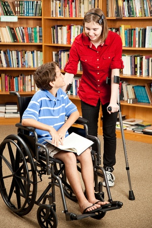 Disabled teen with forearm crutches, talking to a little boy in a wheelchair.  They are in the library.