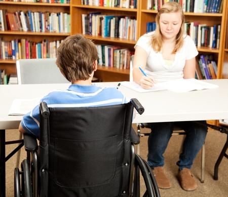 ni�o discapacitado: Estudiante discapacitado en la biblioteca del colegio, estudiando con un compa�ero de clase.  Centrarse en el ni�o en la silla de ruedas.