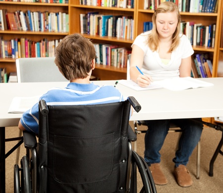 Disabled student in the school library, studying with a classmate.  Focus on the boy in the wheelchair.