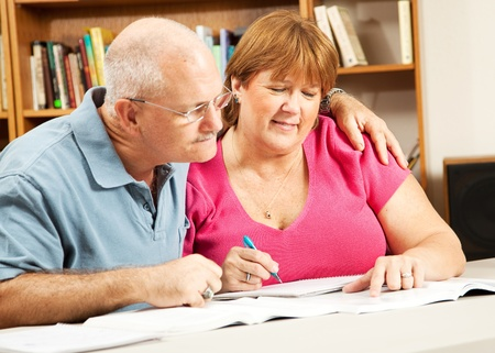 Mature couple in adult education, studying at the library.   photo