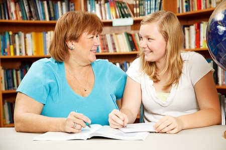 overweight students: Mother or teacher helping a teenage girl study in the school library.