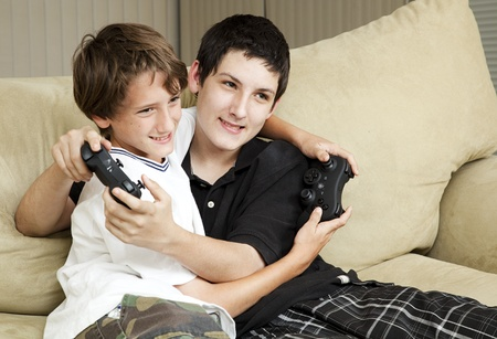 Two affectionate brothers playing video games together.   photo