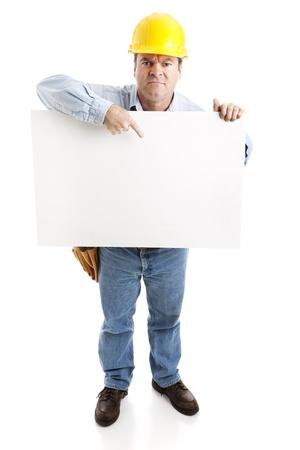 怒っている建設労働者は、空白の白い看板を持っています。完全なボディ、白で隔離されます。