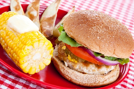 Healthy turkey burger on whole grain bun, with baked potato wedges and corn on the cob, against a red and white checked table cloth.