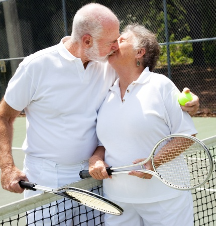 Romatic senior couple kissing on the tennis court. photo