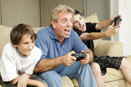 Uncle and his two nephews playing video games together.  Could also be father and sons.   photo