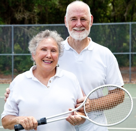 Portrait of an active senior couple on the tennis courts.   photo