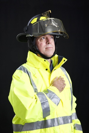 allegiance: Firefighter with his hand over his heart, pledging allegiance to the flag.   Stock Photo