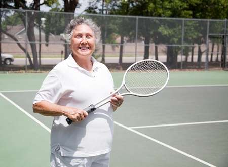 Active senior woman on the tennis courts. Stock Photo