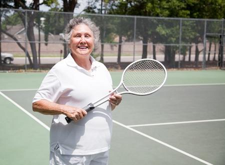 Active senior woman on the tennis courts. photo