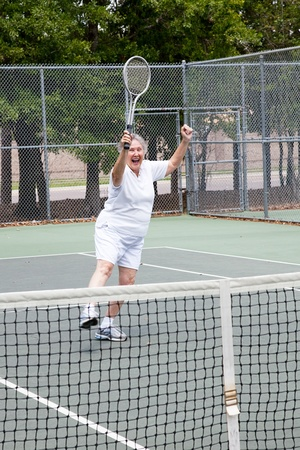 Senior woman excited about winning a tennis match.   photo