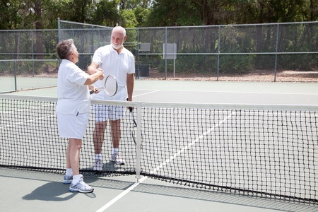 Senior tennis players shake hands over the net.  Wide shot with room for text. Stock Photo - 9596431