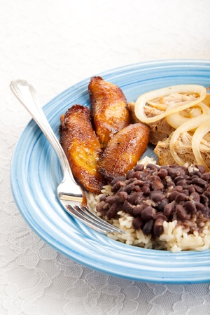 Traditional Cuban meal with sweet plantains, black beans and rice, and roast pork.
