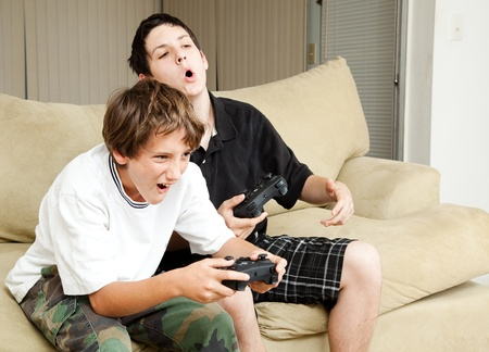 playing video games: Two boys playing video games with intense competition.