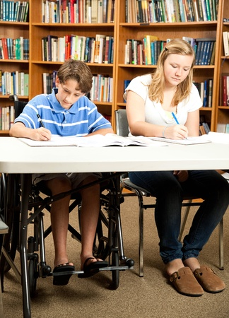 Disabled boy and a friend doing homework in the school library.