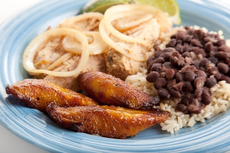 Closeup of Cuban dinner with focus on fried sweet plantains.  Marinated roast pork with black beans and rice complete the meal.   photo