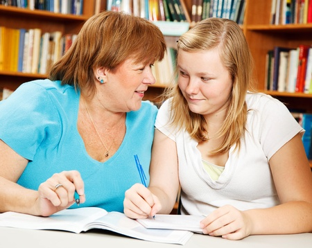 Mother or teacher helping a teenage girl with her homework.   Stock Photo