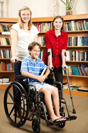 three persons: Group of teens in the library - one is in a wheelchair, one is on hand crutches.