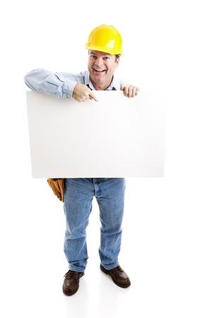 幸せな建設労働者は、空白の白い印を指しています。フルボディの白で隔離されます。